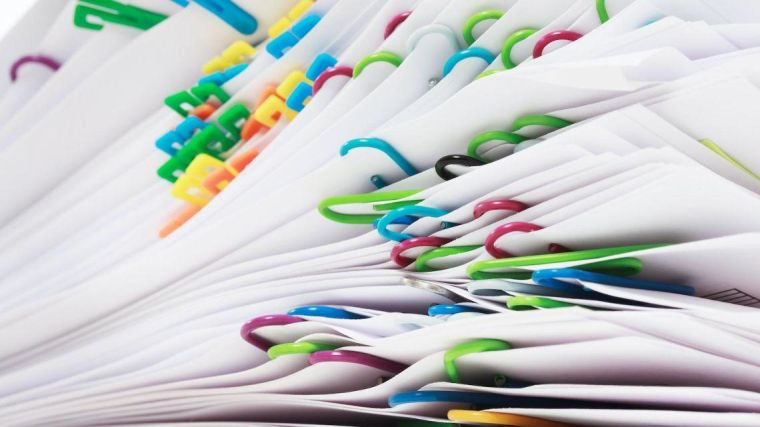 A pile of papers with multicoloured paper clips