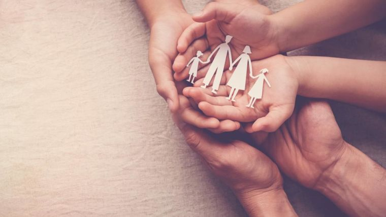 three sets of hands, palms up on top of one another, holding a paper cut out of a family.