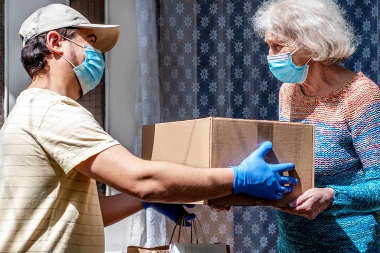 Young male volunteer in mask gives an elderly woman boxes with food near her house. Son helps a single elderly mother. Family support, caring. Quarantined, isolated. Coronavirus covid-19. Donation