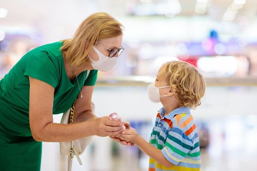 Woman bent down putting hand sanitizer into young boy's hands. Both wearing masks.