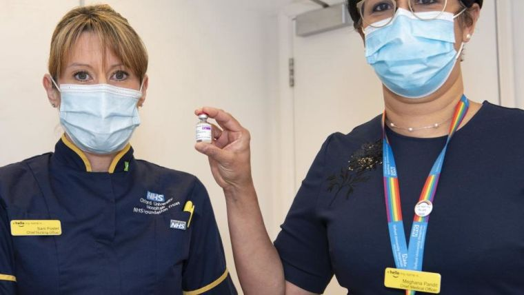 Nurses Sam Foster and Meghana Pandit display a vial of the Oxford coronavirus vaccine