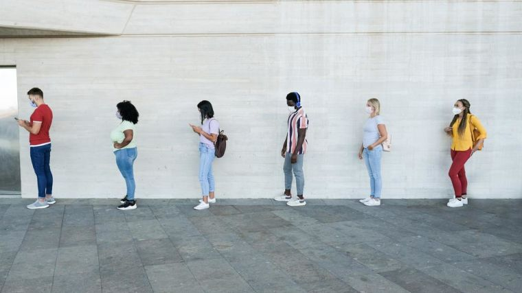 Multiracial people standing in a queue and waiting - Young people with social distancing and wearing protective face masks - Concept of the new normality and social distancing