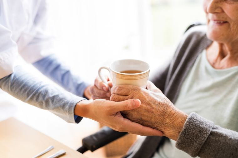 Woman being given a cup of tea in a care home