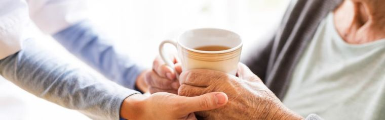 An older woman is given a cup of tea by a carer or support worker