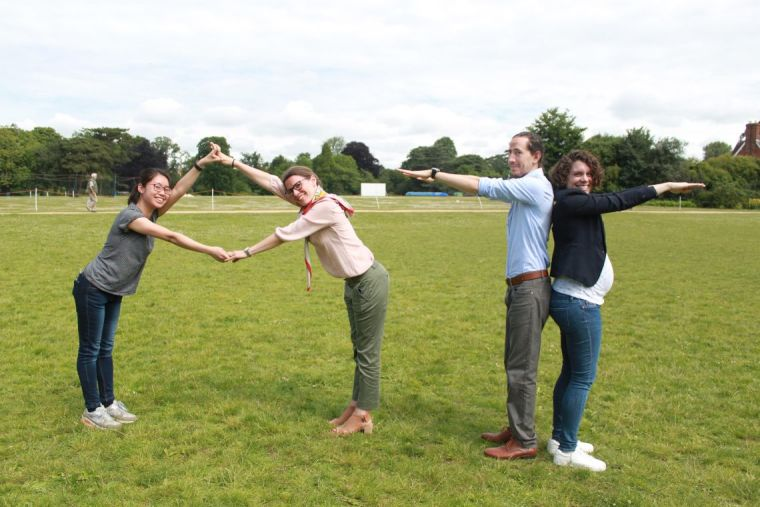Four people standing in a green field making shapes with their arms.