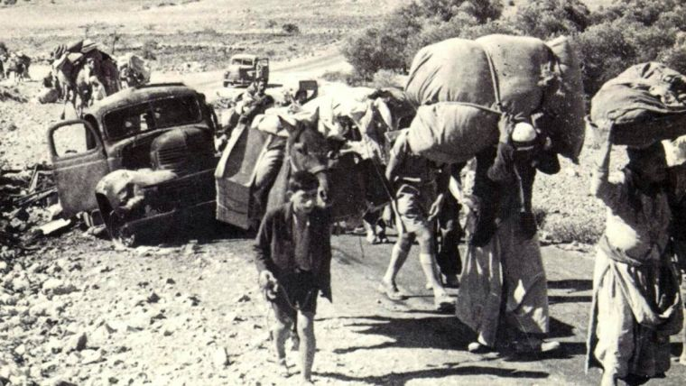 Palestinian refugees carrying their possessions, in 1948
