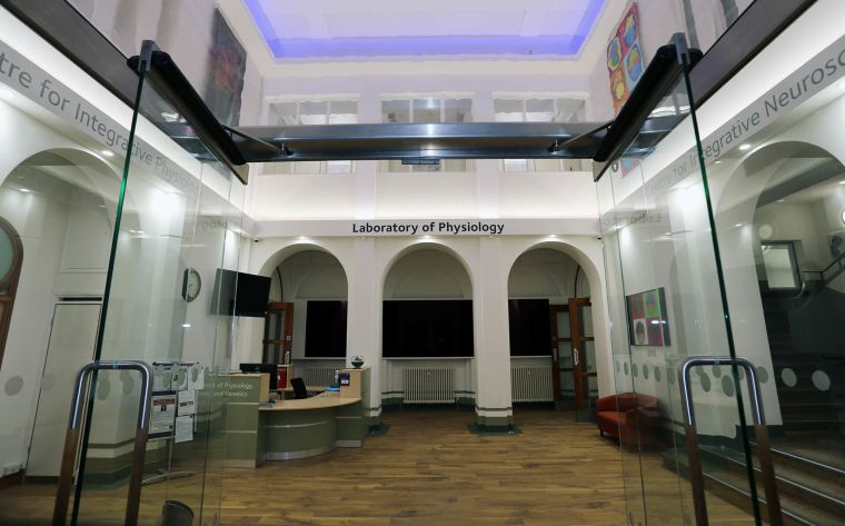 View through the entrance glass doors into reception showing reception desk, guest sofa, three column arches, a video wall and three distinct signs: centre for integrative physiology, Laboratory of Physiology and Centre for Integrative Neuroscience.