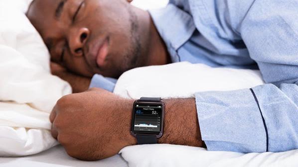 Man asleep wearing sleep tracker on his wrist