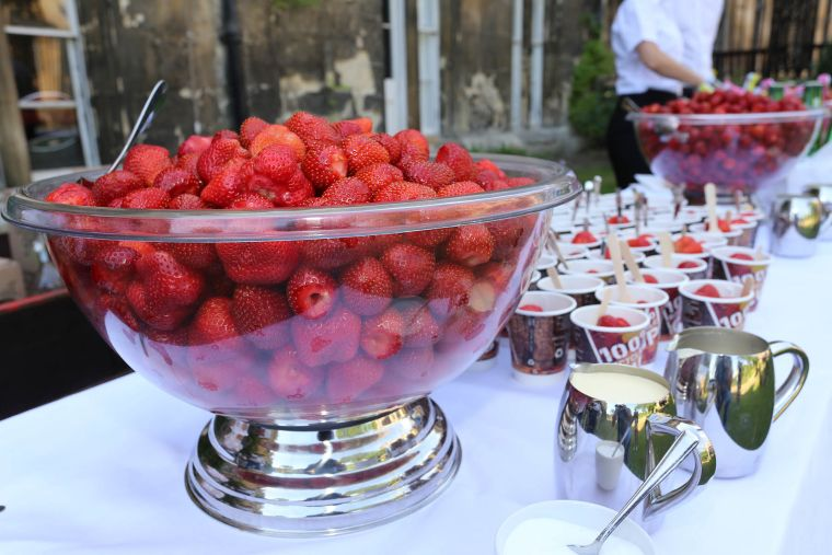 Shot of a bowl of strawberries in the foreground, with cups of strawberries and silver jugs of cream next to it.