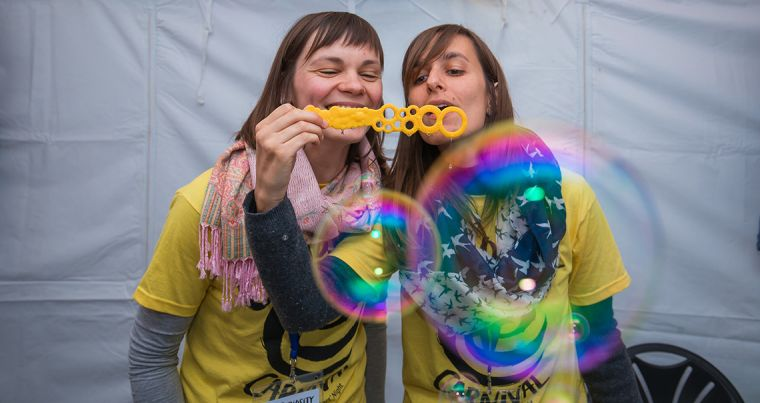 Two women blow bubbles as part of a science experiment