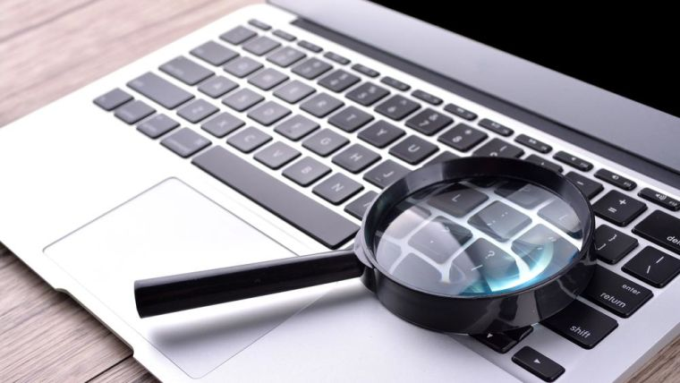 Close-up of laptop and magnifying glass