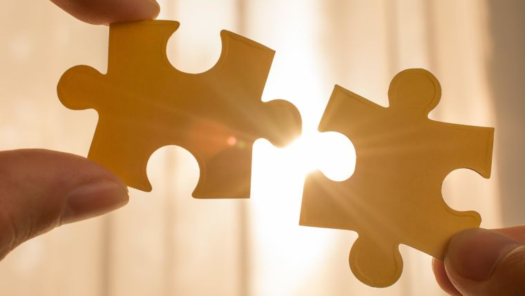 two hands trying to connect couple puzzle piece with sunset background. business strategy concept