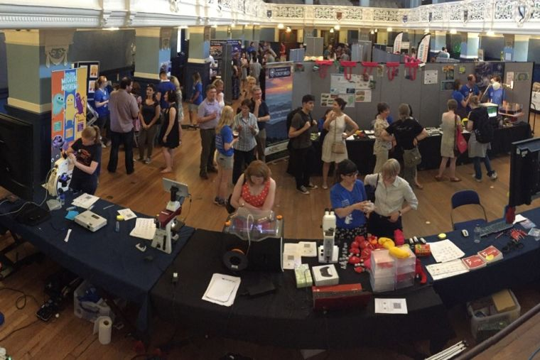 An exhibition/science fair showing numerous people looking at stalls and mingling.