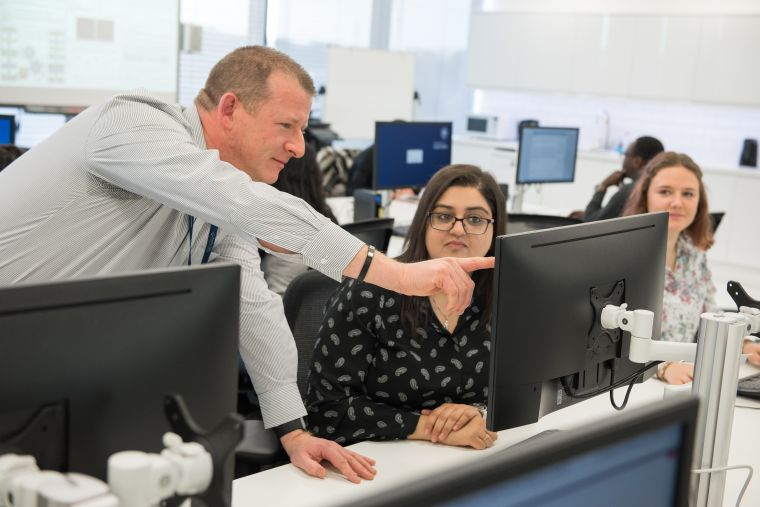 A senior colleague is shown pointing out something on the computer screen to a junior colleague in an office setting.