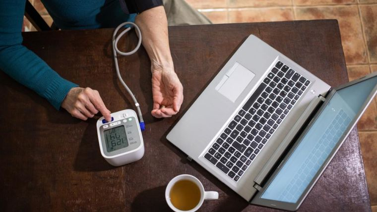 A lady measuring her blood pressure at home using a cuff, and a laptop.