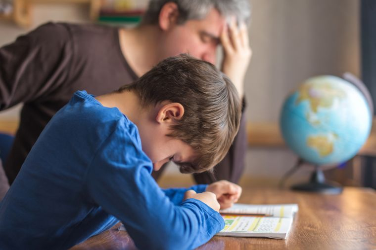 A picture of a man and his child both looking stressed with homeschooling.