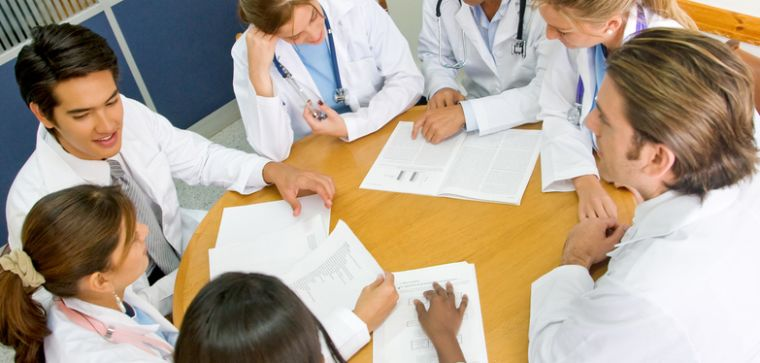 Medical students sitting at a round table working collaboratively on a project