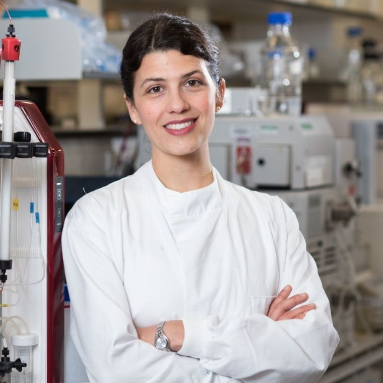 Elena Seiradake smiles and crosses her arms wearing a lab coat in the lab