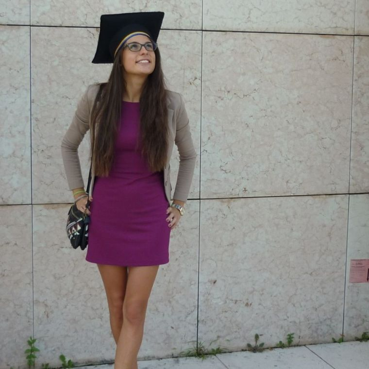 Michela Serena grins and looks to the sky whilst wearing a graduate mortar board
