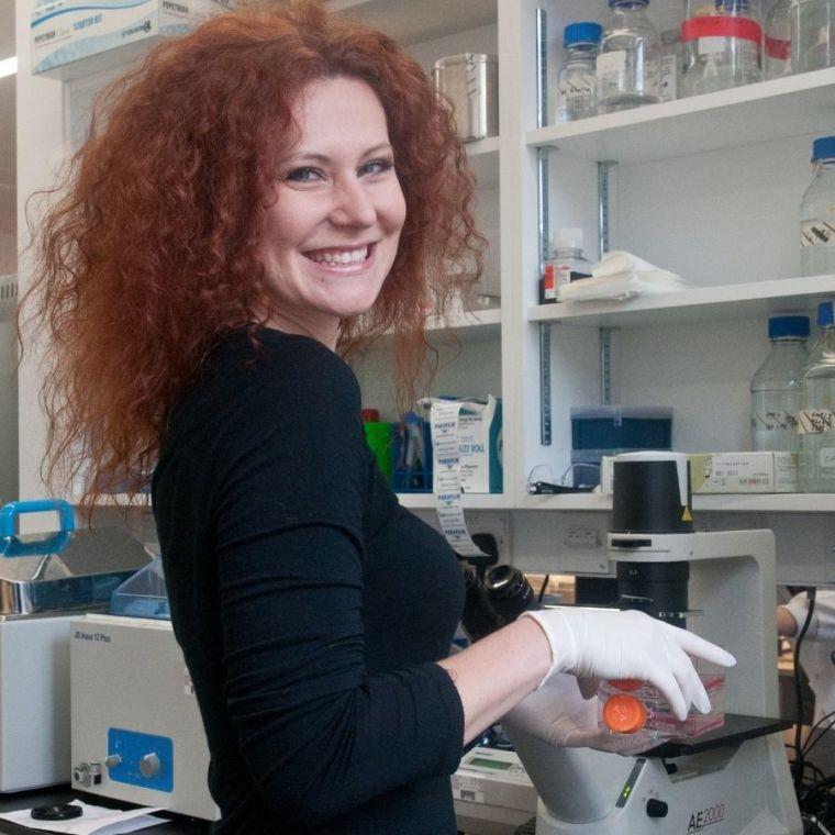 Monika Gullerova smiles as she looks around from her microscope