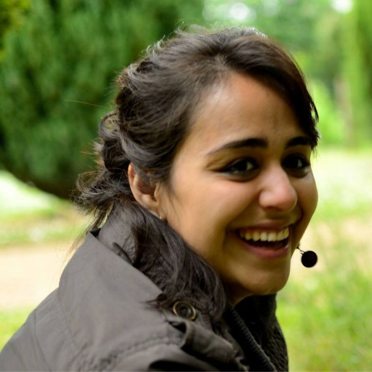 Nahid Zokaei wears a headset and laughs in a leafy outdoor setting