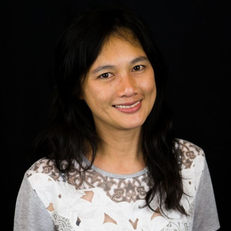 Phaik Yeong Cheah smiles in front of a dark background