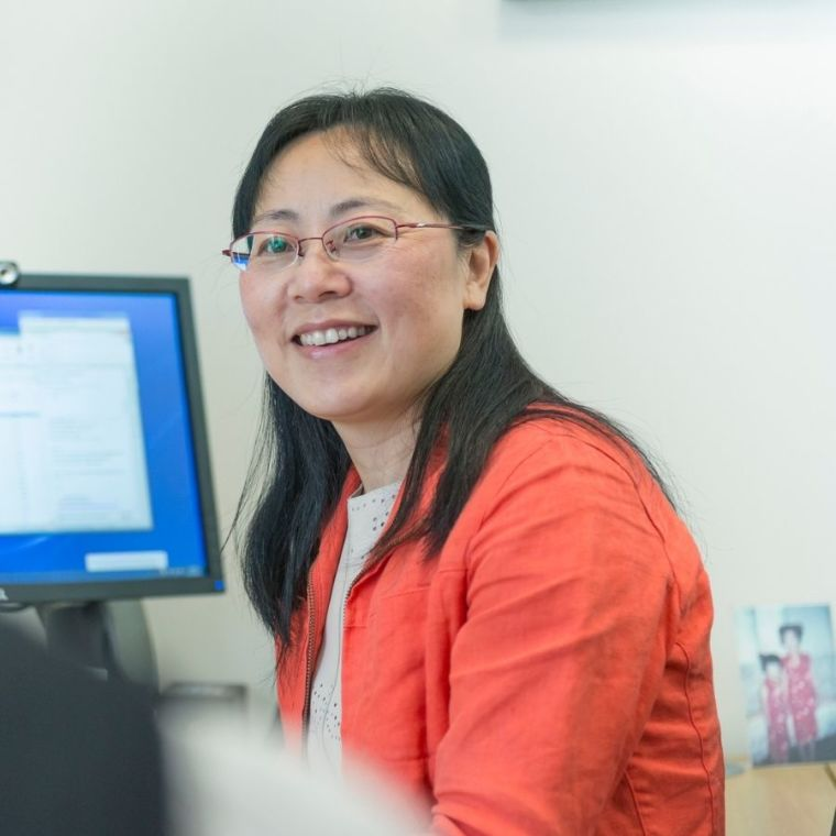 Professor Xin Lu wears a bright orange jacket in a work setting