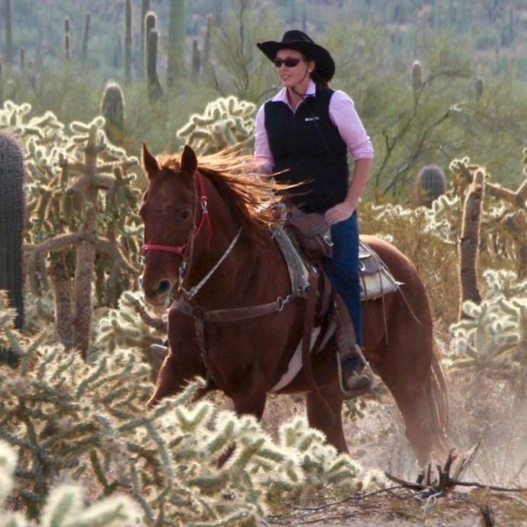 Stephanie Georgina Dakin rides a horse through a sunny, dusty cactus-strewn landscape