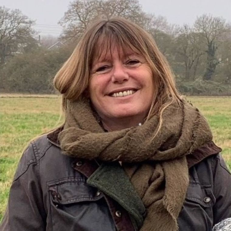 Susan Patchett smiles happily wearing a coat and scarf in the great outdoors