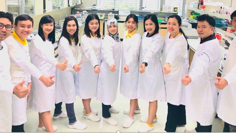 Molecular Malaria Lab members in a semi-circle doing thumbs up.