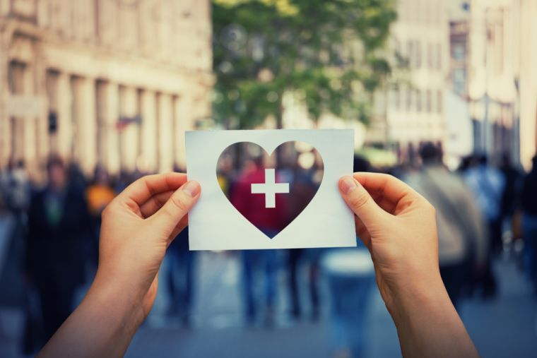 close up of hands holding a white postcard with a see-through heart in the middle and a first aid cross in the centre (against a building backdrop)
