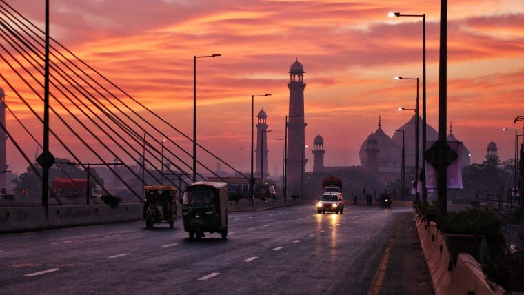 Vehicles driving on a bridge with a mosque and sunset in the background.