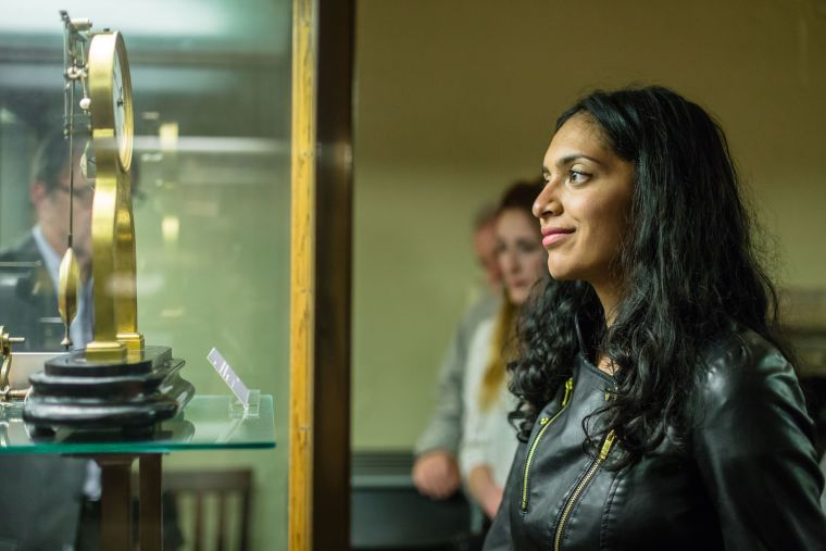 Woman looking at artefacts in museum glass cabinet