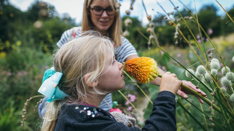 Young blonde girl smelling flower in Oxford's Botanical Garden, stood next to mother