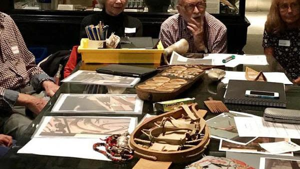Group of older people sat around table at Pitt Rivers Museum