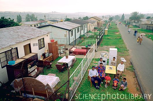 South African family with their possessions assembled outside their house (stock photo)