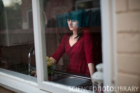 Sad woman looking out of kitchen window (stock photo)