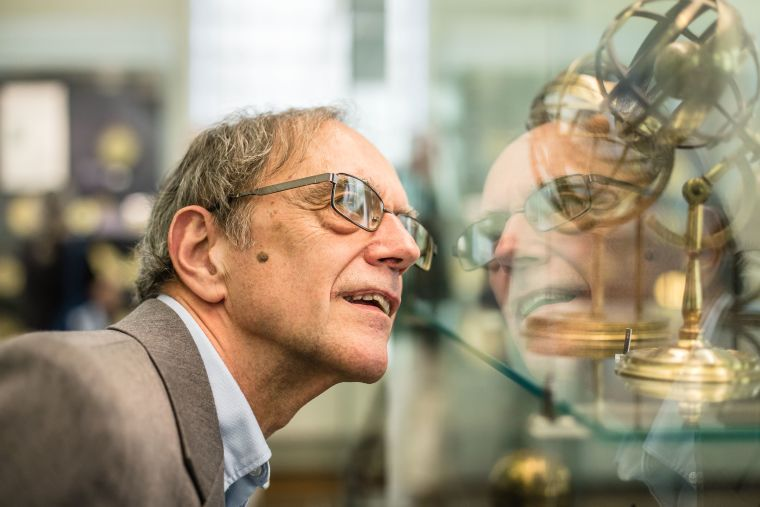 Man looking into glass cabinet with artefacts in museum