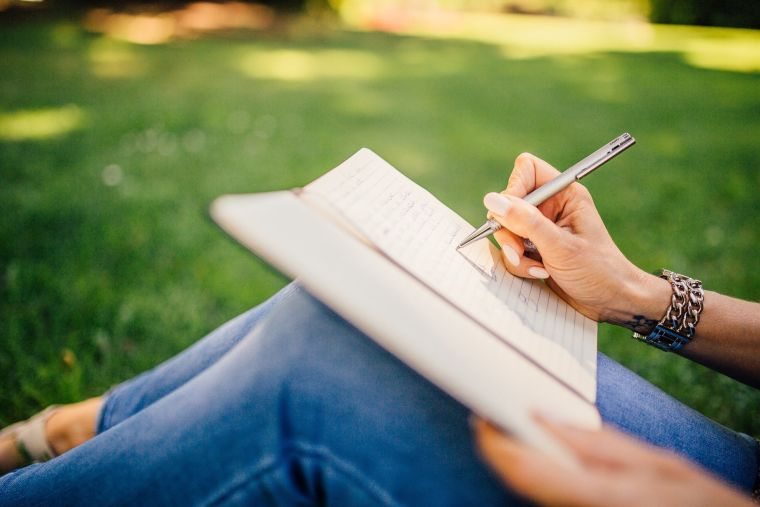 Close up on woman sat outside writing in notepad. No face in view- legs and hands only