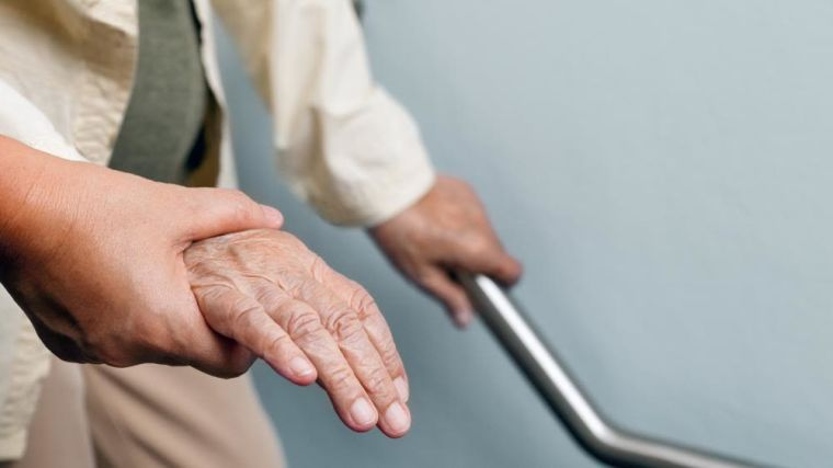 A nurse helping an elderly person to walk down some stairs