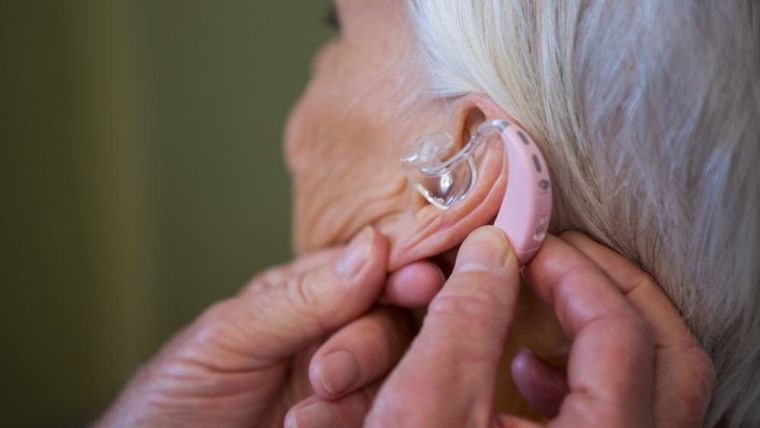A woman is fitted with a hearing aid
