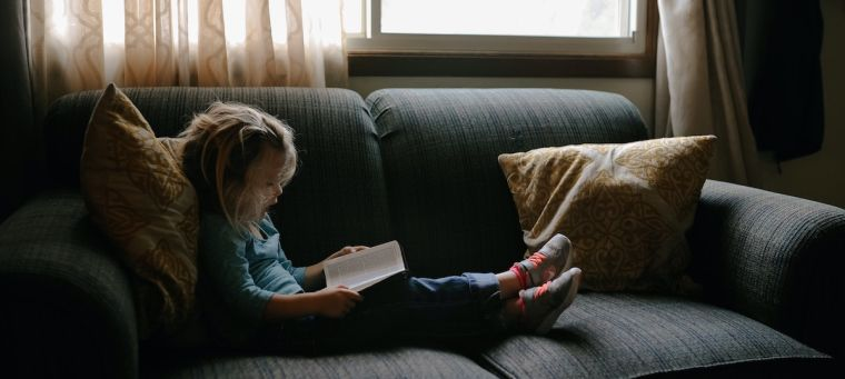 Young girl sitting on grey sofa reading a book.
