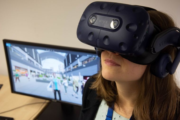 Woman wearing a virtual reality headset next to a computer screen