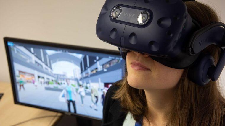 Woman wearing a virtual reality headset next to a computer screen