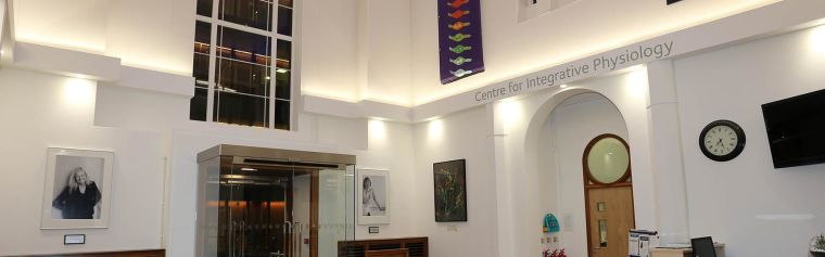 The whole reception interior facing back towards the glass door front entrance, including sofas either side of the front door, the Facilities office, reception desk, Centre for Integrative Physiology Sign and artwork on the walls.