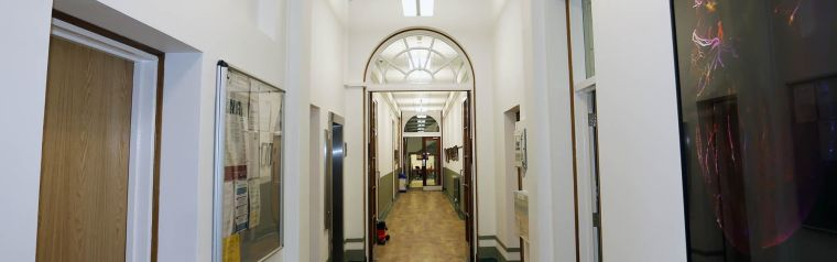 Long view down corridor shows artwork and noticeboards on walls, each connecting door is open showing full length.