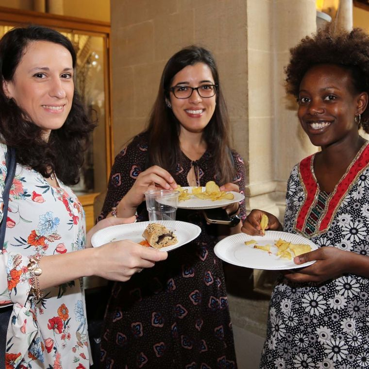Three female postdocs with plates of food in a small group