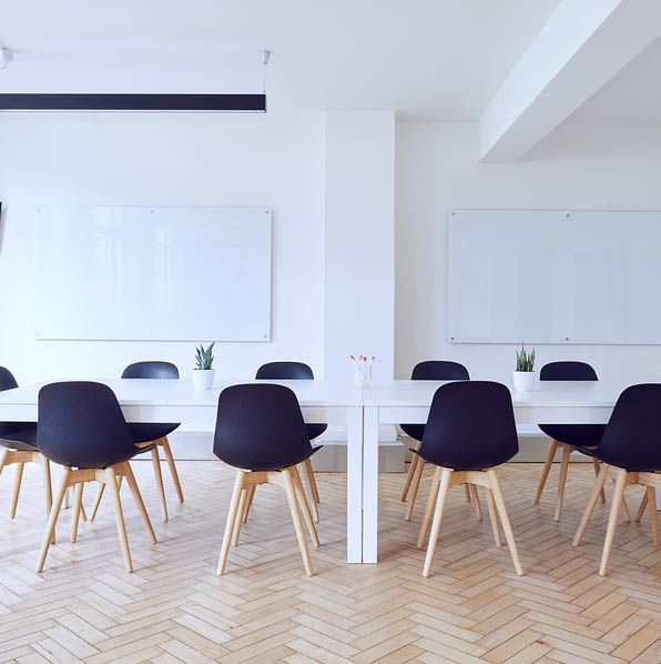 A seminar room with two whiteboards and a long table with chairs.