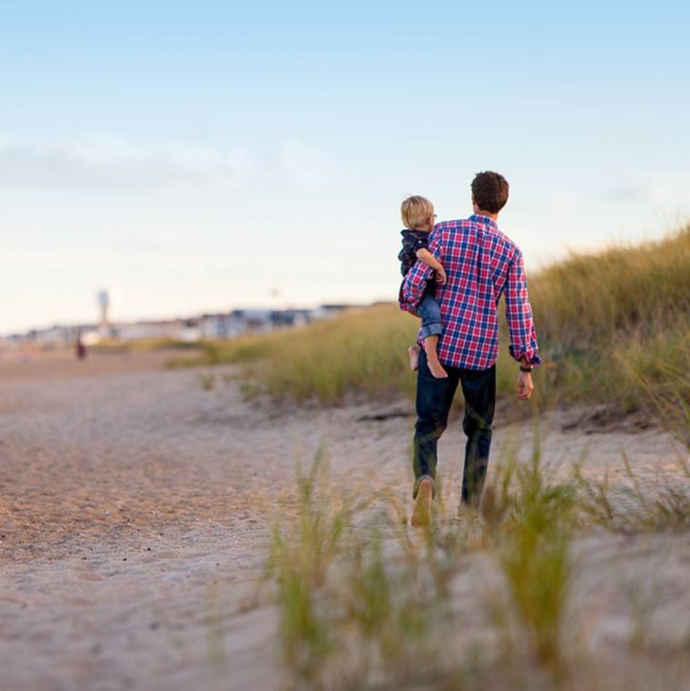 A father and son walking on the beach