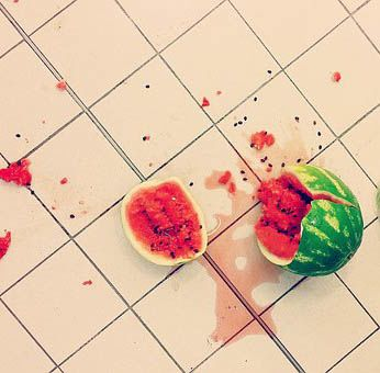 A watermelon broken in two on the floor